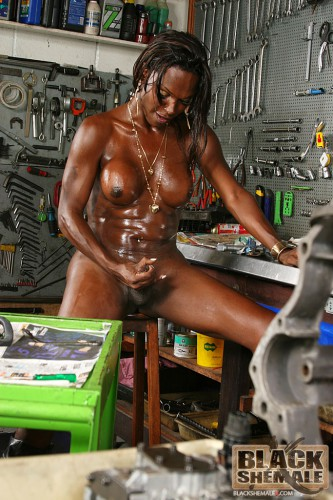 slutty black shemale jerks off in a garage